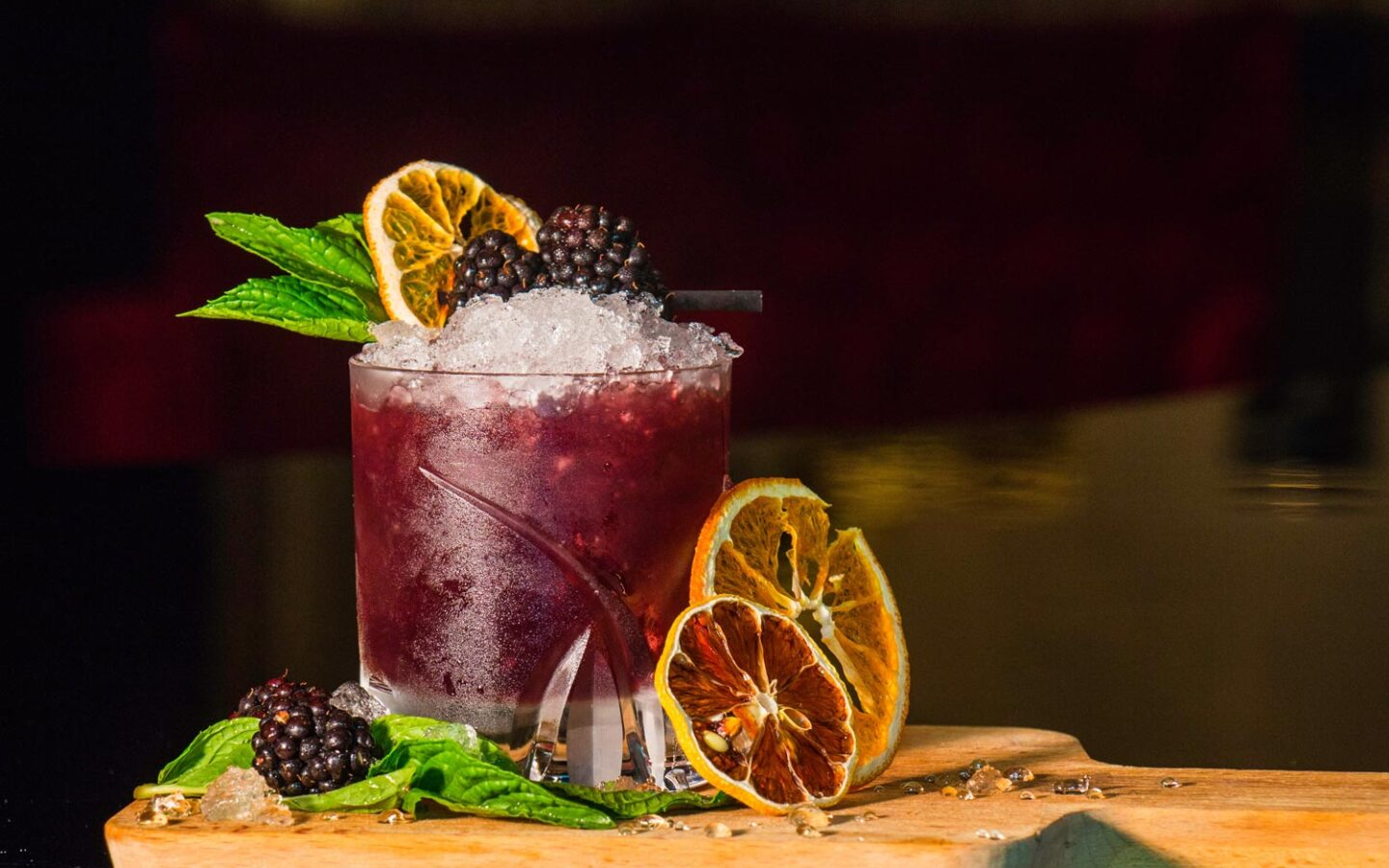cocktail set on wooden cutting board with blackberries and oranges as garnish